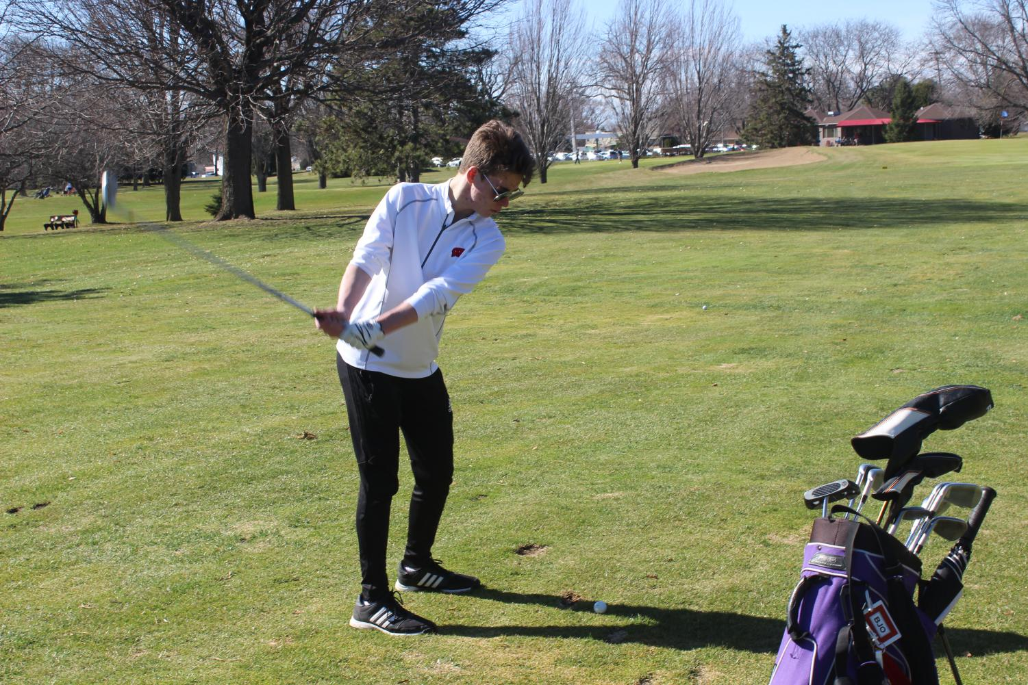 Junior Bryn Ostby practices his swing at the Monona Golf Course, where the team practices.  The biggest challenges, coach Tina Lindsey said, is the size of the team, as it is made up of only three golfers, and who also compete as individuals.