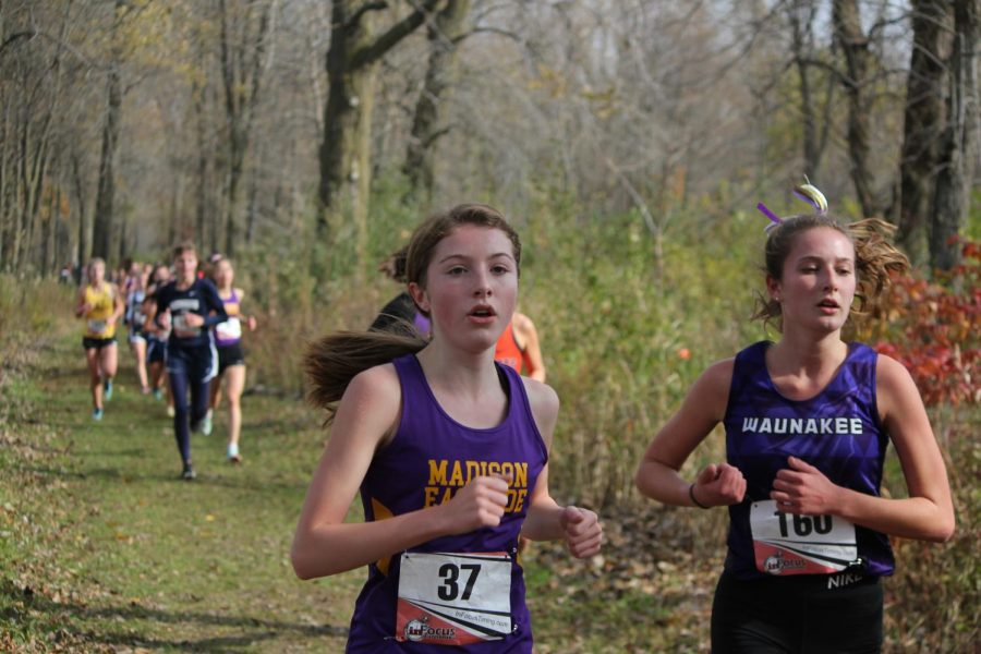 Varsity runner, freshman Raena Keckhaver keeps a slight lead on a runner from Waunakee, over half way through the race. Keckhaver finished the race with a time of 21:33.
